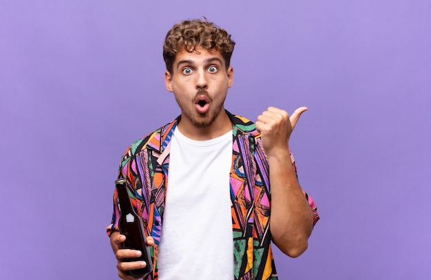 Jonge man kijkt verbaasd in ongeloof, wijst naar een object aan de zijkant en zegt wow, ongelooflijk. vakantie concept