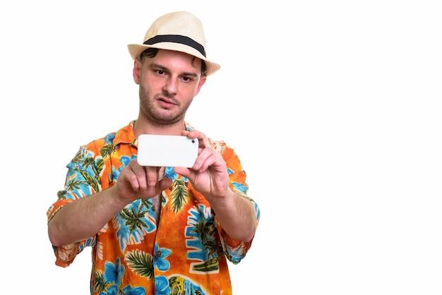 Jonge man kijkt verveeld tijdens het nemen van foto met