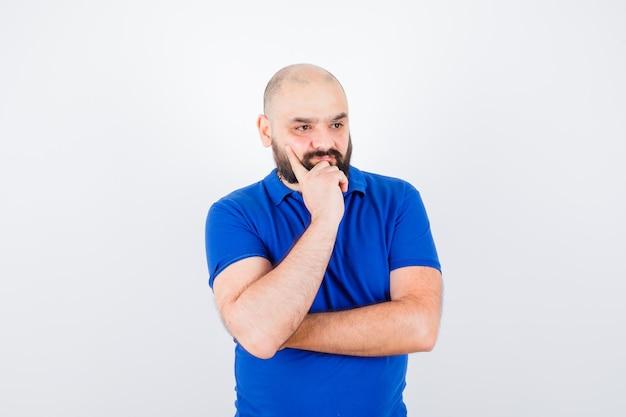 Jonge man kijkt weg terwijl hij naar zijn hand leunt in een blauw shirt en peinzend kijkt, vooraanzicht.