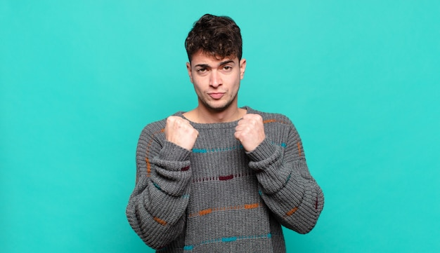 Jonge man kijkt zelfverzekerd, boos, sterk en agressief, met vuisten klaar om te vechten in bokspositie