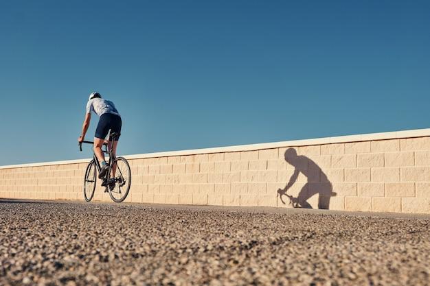 Jonge man klimmen met een wedstrijdfiets op een kustweg