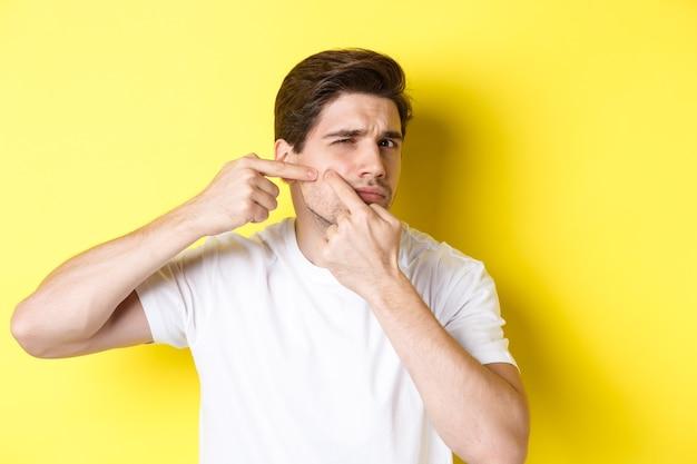 Jonge man knalt een puistje op de wang, staande op een gele achtergrond. concept huidverzorging en acne.