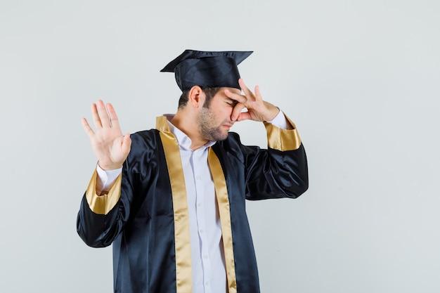 Jonge man knijpen neus vanwege slechte geur in afgestudeerde uniform en walgt op zoek. vooraanzicht.