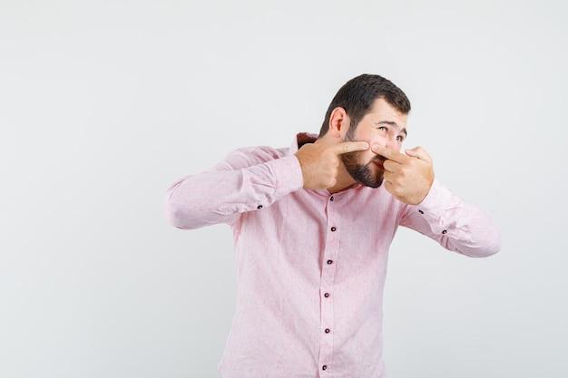 Jonge man knijpen puistje op wang in roze shirt en op zoek geïrriteerd