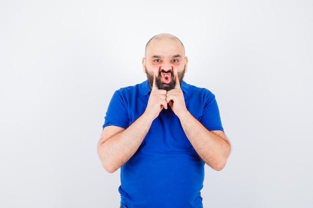 Jonge man knijpen zijn wangen met vingers in blauw shirt vooraanzicht.