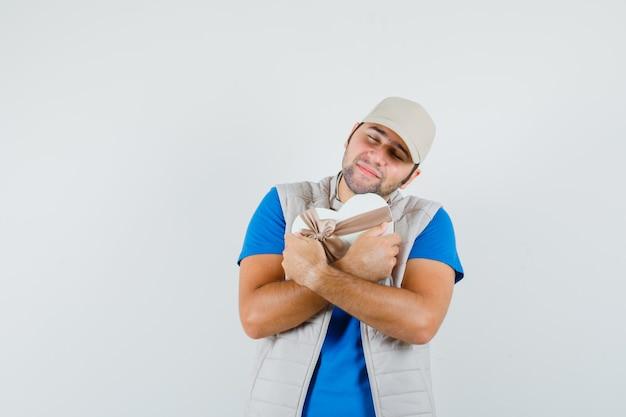 Jonge man knuffelen geschenkdoos in t-shirt, jas en rustig op zoek. vooraanzicht.