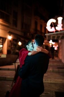 Jonge man knuffelen met lachende vrouw op straat in de avond