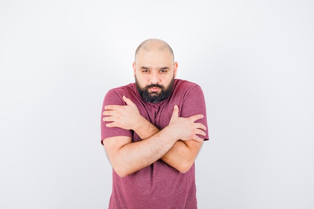Jonge man knuffelt zichzelf in een roze t-shirt en ziet er koud uit. vooraanzicht.