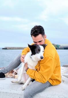 Jonge man knuffelt zijn border collie-hond met de zee op de achtergrond