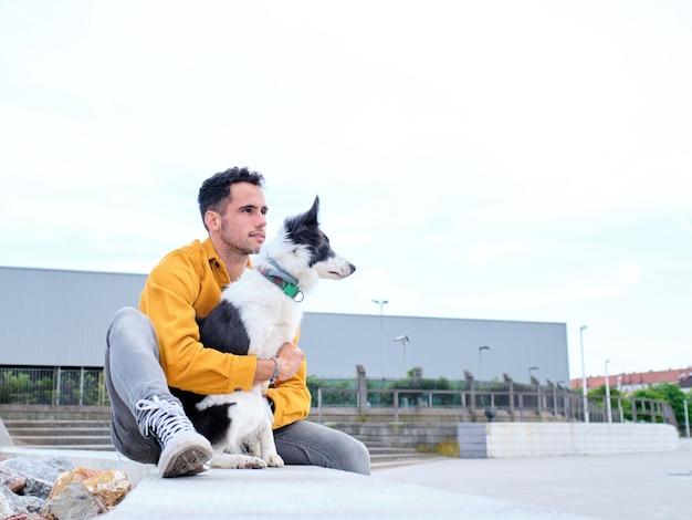 Jonge man knuffelt zijn border collie-hond