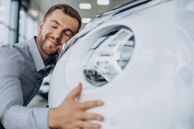 Jonge man knuffelt zijn nieuwe auto in een autosalon