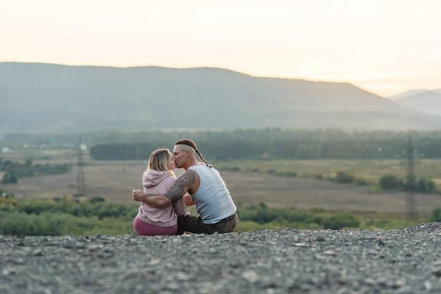 Jonge man koestert zijn vriendin op de berg bij zonsondergang