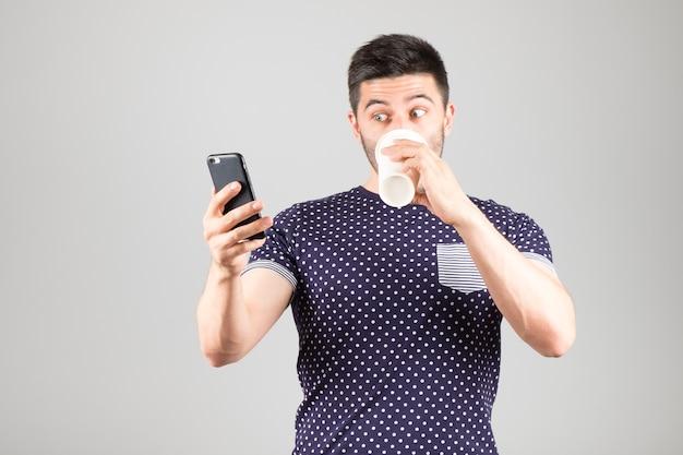 Jonge man koffie drinken en zijn smartphone gebruiken