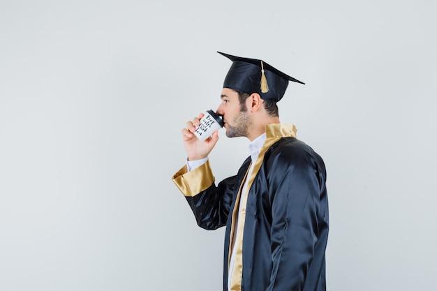 Jonge man koffie drinken in afgestudeerde uniform en peinzend op zoek.