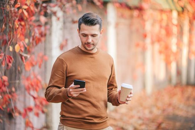 Jonge man koffie drinken in herfst park buitenshuis