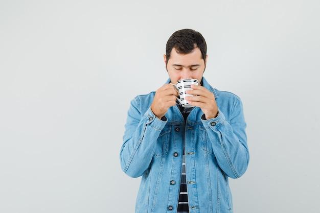 Jonge man koffie drinken in t-shirt, jas en op zoek verrukt