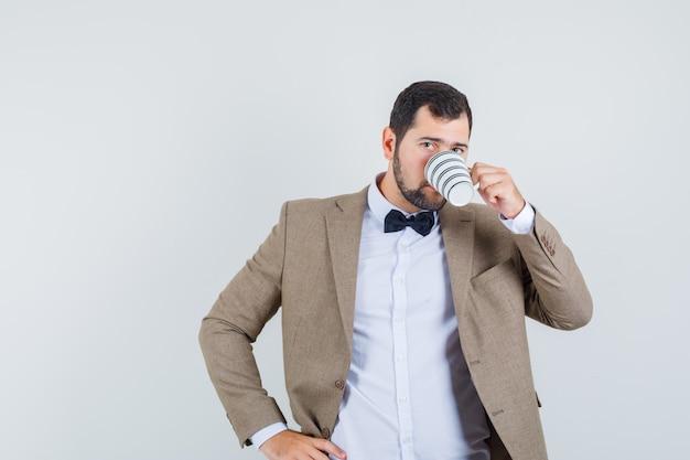 Jonge man koffie drinken met hand op taille in pak, vooraanzicht.