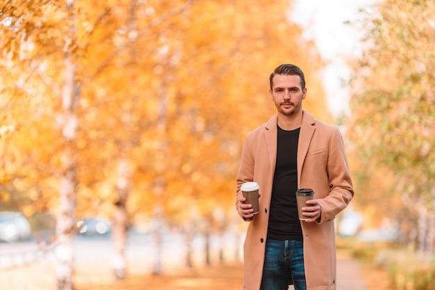 Jonge man koffie drinken met telefoon in herfst park buitenshuis