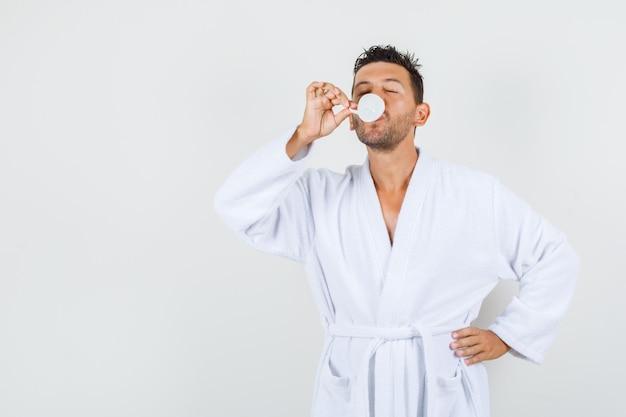 Jonge man koffie drinken na bad in witte badjas vooraanzicht.