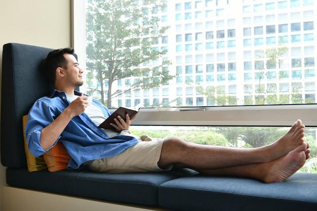 Jonge man koffie drinken zittend op de bank thuis met het boek in zijn hand