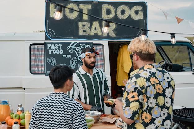 Jonge man kookt en verkoopt hotdogs aan jonge mensen terwijl ze buiten staan