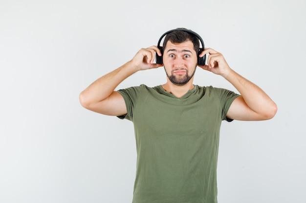 Jonge man koptelefoon in groen t-shirt aan te passen en verbaasd op zoek