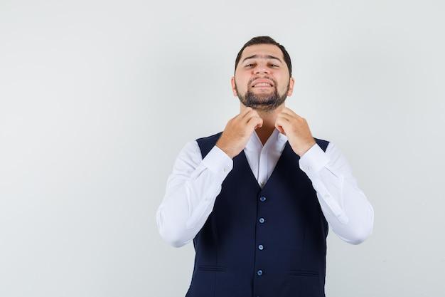 Jonge man kraag in overhemd, vest aan te passen en op zoek naar vertrouwen