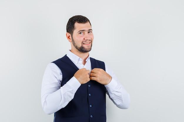 Jonge man kraag van vest in pak aanpassen en ziet er leuk uit