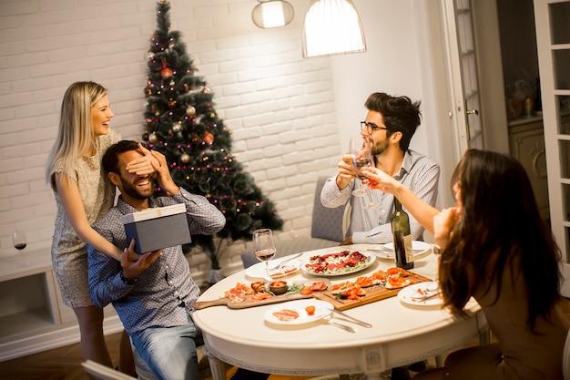 Jonge man krijgt cadeau van liefhebbende vrouw voor kerstmis of oudejaarsavond