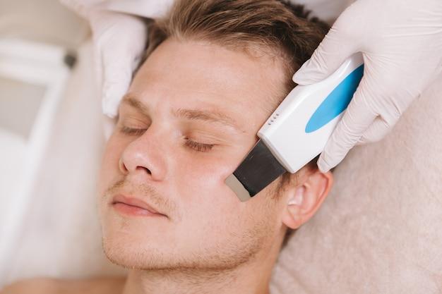 Jonge man krijgt gezichtsverzorgingsbehandeling door schoonheidsspecialist