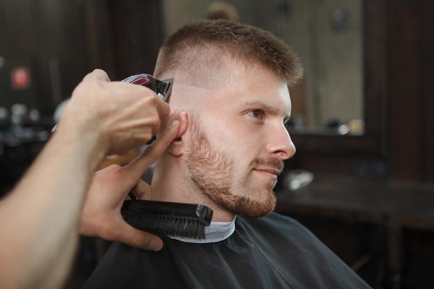 Jonge man krijgt nieuw kapsel bij kapperszaak
