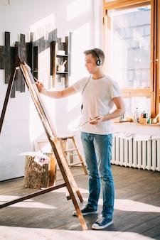 Jonge man kunstenaar schildert een foto