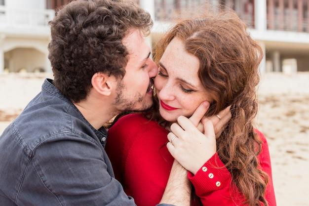 Jonge man kussende vrouw op wang