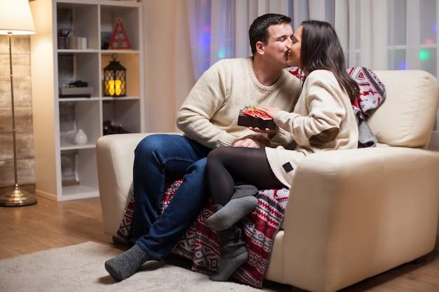 Jonge man kuste zijn vrouw wang op eerste kerstdag na ontvangst van een geschenk.