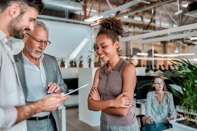Jonge man laat iets op een digitale tablet zien aan zijn collega's terwijl hij samen staat