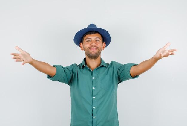 Jonge man lachend met open armen voor knuffel in shirt