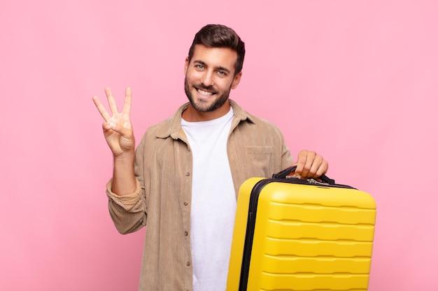 Jonge man lacht en ziet er vriendelijk uit, met nummer drie of derde met de hand naar voren, aftellend. vakantie concept