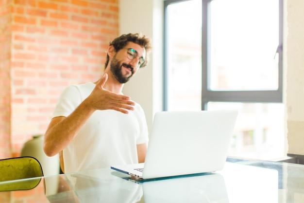 Jonge man lacht, groet je en biedt een handdruk om een succesvolle deal, samenwerkingsconcept te sluiten