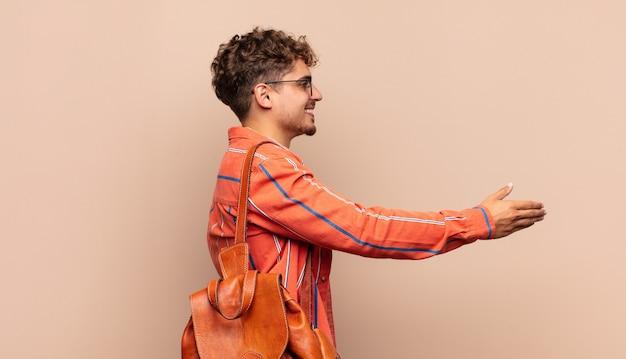 Jonge man lacht, groet u en biedt een geïsoleerde handdruk