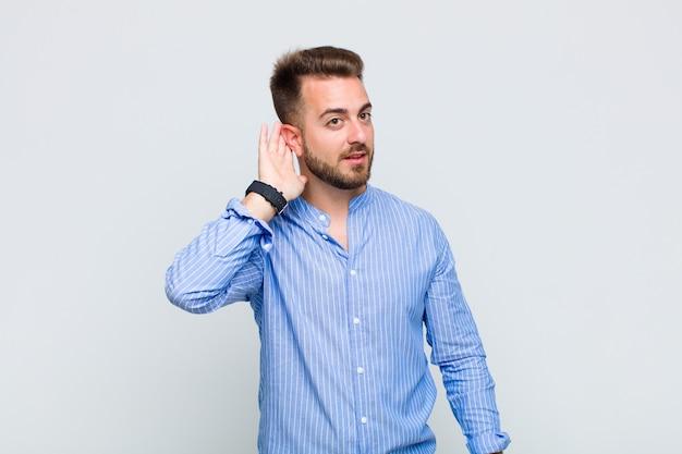 Jonge man lacht, kijkt nieuwsgierig naar de zijkant, probeert te roddelen of een geheim af te luisteren