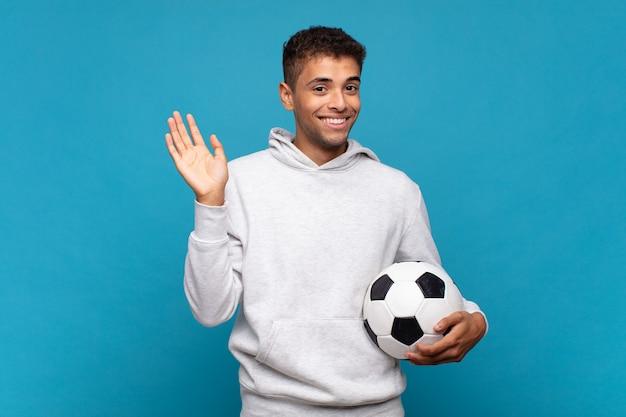 Jonge man lacht vrolijk en opgewekt, zwaait met de hand, verwelkomt en begroet je, of neemt afscheid