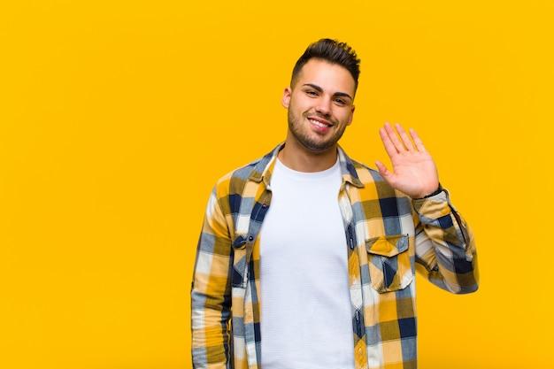 Jonge man lacht vrolijk en vrolijk, zwaait met de hand, heet u welkom en groet u, of neemt afscheid van de oranje muur
