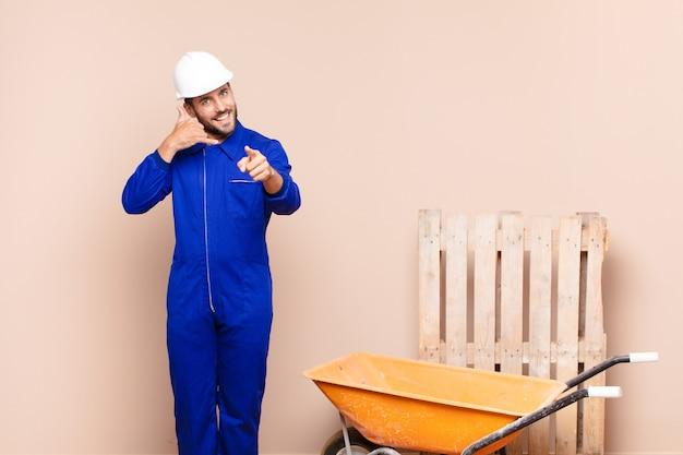 Jonge man lacht vrolijk en wijst naar de camera terwijl je later belt, praten over het bouwconcept van de telefoon