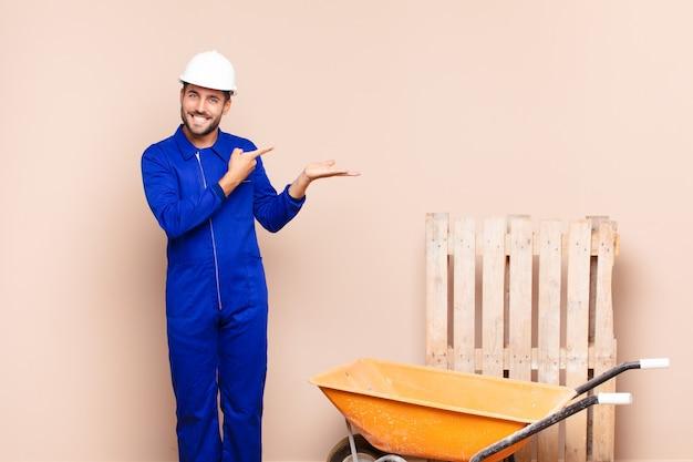 Jonge man lacht vrolijk en wijst naar kopie ruimte op de palm aan de zijkant, het tonen of adverteren van een objectconstructieconcept
