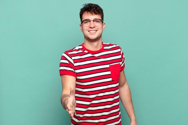 Jonge man lacht, ziet er gelukkig, zelfverzekerd en vriendelijk uit, biedt een handdruk om een deal te sluiten, werkt samen