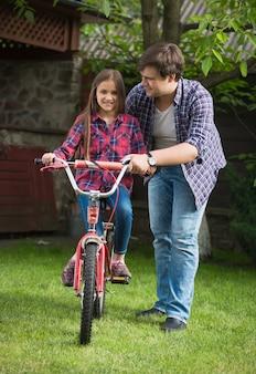 Jonge man leert schattig meisje hoe ze moet fietsen in het park