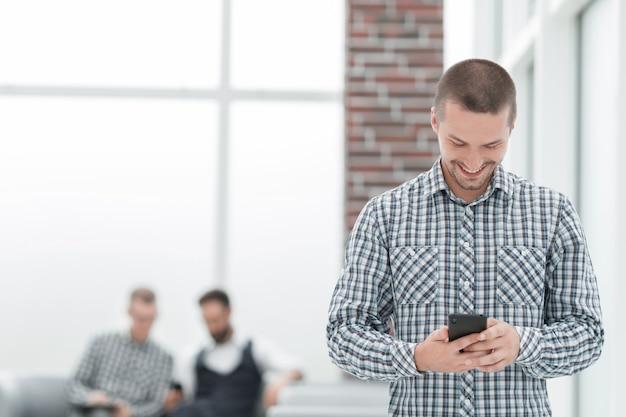 Jonge man leest een sms op zijn smartphone. mensen en technologie