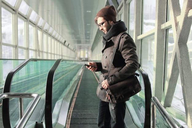 Jonge man leest een sms terwijl hij in de metro staat.