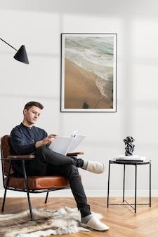 Jonge man leest een verslag in een gezellige leeszaal terwijl hij thuis werkt