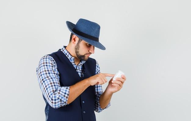 Jonge man leest informatie over fles pillen in shirt, vest, hoed en op zoek gericht.